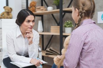 Mujer profesional en Servicio Social escuchando el testimonio de una joven